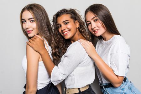 Three beautiful multiethnic women having fun while standing on gray background
