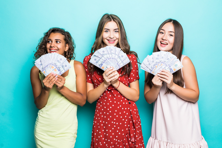 Three beautiful excited three mixed race women in dresses holding money banknotes over blue background Foto de archivo