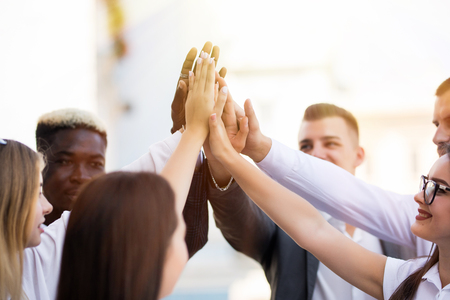 Happy multiracial business team giving a high fives gesture as they laugh and cheer their success