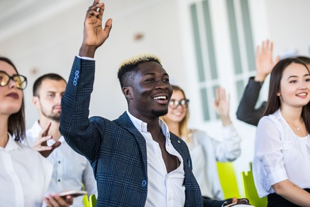 I have a question. Group of people sitting at the chairs in conference hall, raising their hands. Business and Entrepreneurship event. Stock fotó