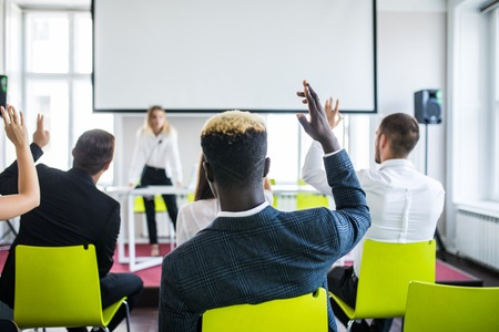 Audience raising hands up while businesswoman is speaking in training at the office.
