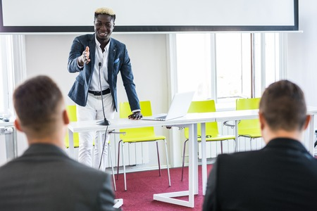 Young man raising hand to ask question, boss leader businessman presenting new project to multiracial millennial colleagues during briefing. Corporate training coaching, conference and seminar concept
