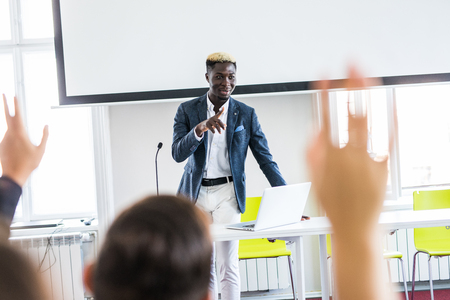 African american businessman giving presentation discussing project with multi-ethnic group at corporate training, black teaching coach answering questions asked by audience during business seminar