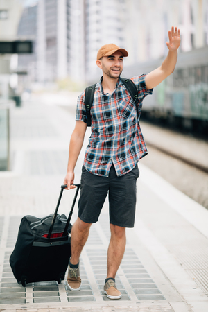 Portrait of handsome man raising hand looking away and smiling at train station Standard-Bild