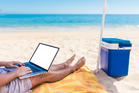 Young man with laptop with copy space blank lying on the beach under umbrella on vocation