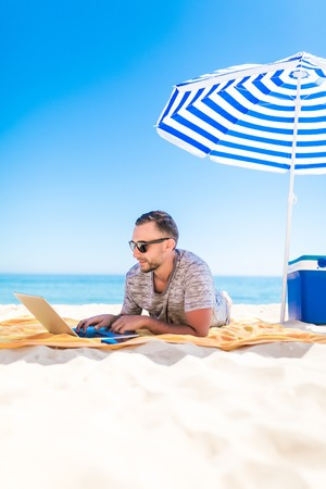 freelancer, happy successful businessman with laptop on the beach, blue sky Stock Photo