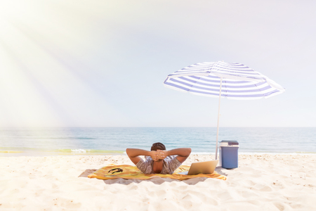 Young man is resting under umbrella on a sun overlooking the sea on the beach