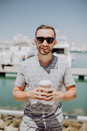 Young man in sunglasses drink coffee to go on summer street with yacht harbor on background.