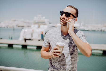 Young handsome man in sunglasses drink coffee to go and talk mobile phone on summer street with yacht harbor on background.
