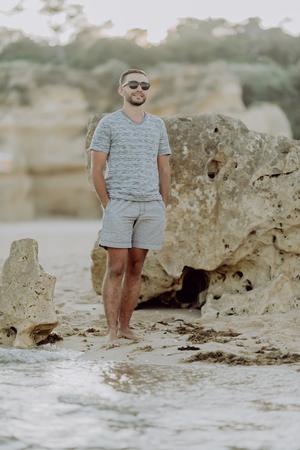 Portrait of attractive man on the beach walking, happy healthy man model beach rocks ocean holliday