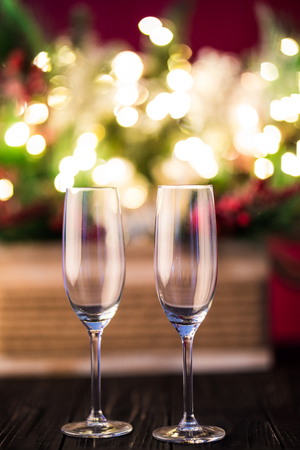 New year holiday or christmas green background. Branches of christmas trees decorated with golden lights, garlands, toys and empty champagne glasses. New Year greeting concept