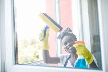 Smiling afro american woman cleaning glass window with squeegee Stock Photo