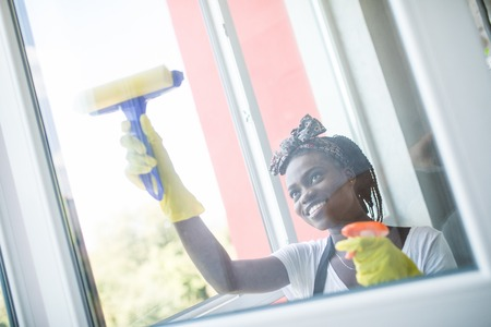 Smiling afro american woman cleaning glass window with squeegee Foto de archivo