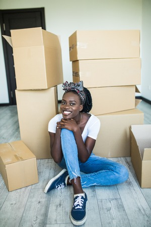 Charming young african girl standing on her knees on the floor and smiling at the camera while taking plates out of the box