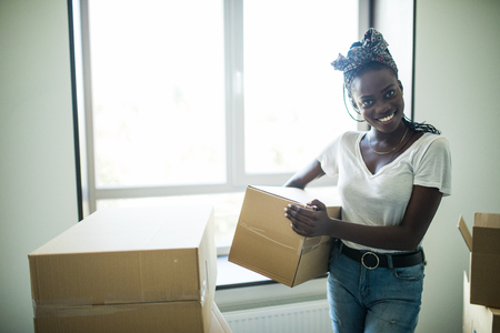 Attractive young african woman is moving, looking at each other and smiling while standing among cardboard boxes. Stock Photo