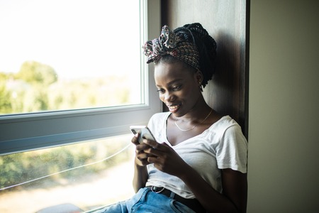 Smiling afro american woman sitting on the windowsill and writing message on phone at home