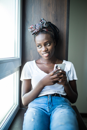 Young african woman typing on mobile phone on windowsill Stock Photo