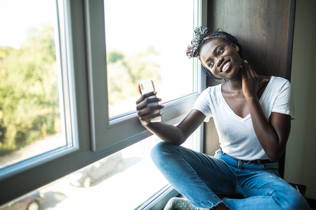 Happy afro american woman in t-shirt sitting on the windowsill and making selfie on smartphone while waving at camera Stock Photo