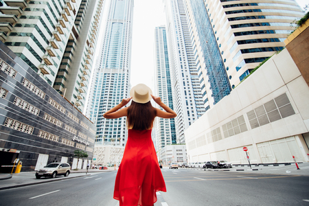 Rear view of young woman in red summer dress holding straw hat while walking near skycrapers on downtown of modern city.