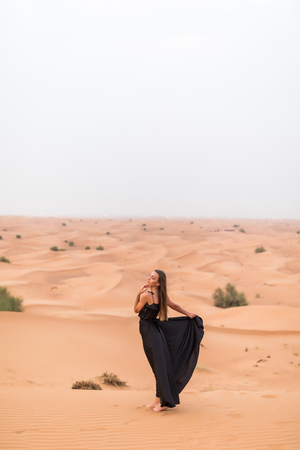 Beautiful pretty woman in black dress on a dune of desert Banque d'images