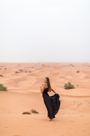 Young woman in black dress stands on dune in desert at sunny hot day Stock Photo