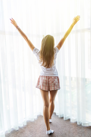 Rear view of woman stretching in bed after wake up in morning with sunlight Stock fotó