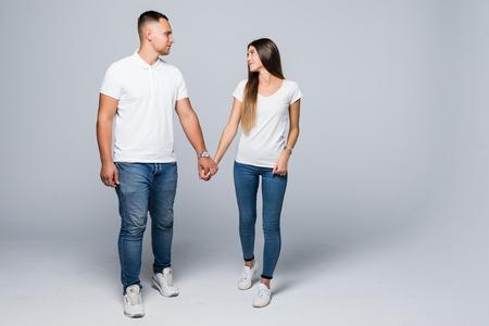 Glückliches Paar, das Händchen hält und auf grauem Hintergrund isoliert geht