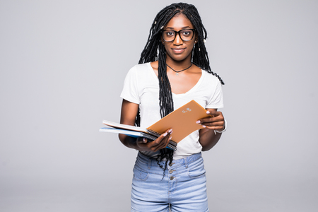 Retrato de una sonriente mujer afroamericana sosteniendo el cuaderno con lápiz sobre fondo gris