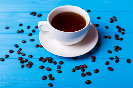 Small espresso cup with coffee beans on blue background Stock Photo