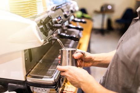 barista steaming milk in coffeeshop close up
