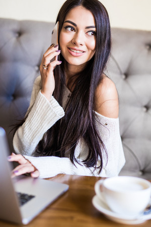 Young woman talking on mobile phone and using laptop Archivio Fotografico