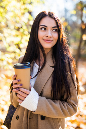 Young woman walking in the autumn city street and drinking take away coffee in paper cup. 免版税图像