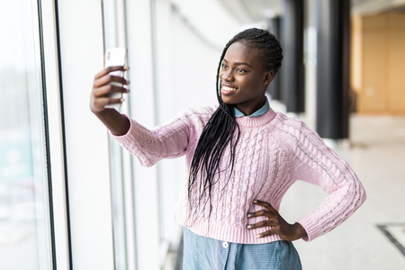 Young african woman take selfie on mobile phone in front of panoramic windows in business center. 版權商用圖片