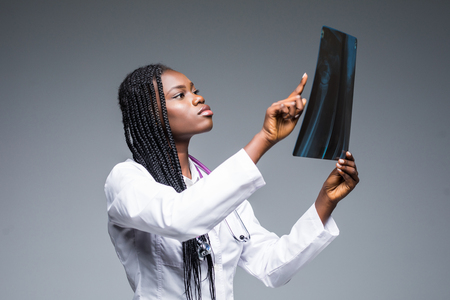 Closeup portrait of doctor woman healthcare personnel with white labcoat, looking at full body x-ray radiographic image, ct scan, mri, isolated gray background. Reklamní fotografie