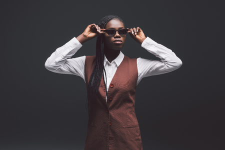 Stylish young african woman in sunglasses gainst dark background. Stock fotó