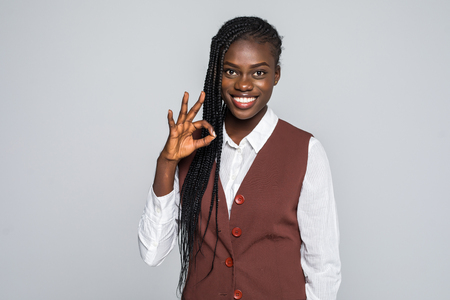 Portrait of afro american woman gesturing ok sign with fingers looking at camera isolated on grey background Stock fotó
