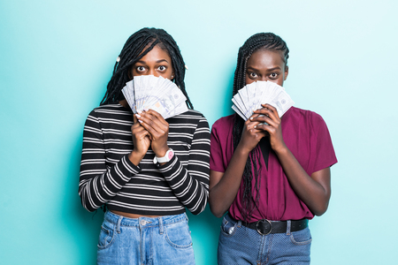 Photo of african american womens covering their faces with dollar banknotes isolated over blue background