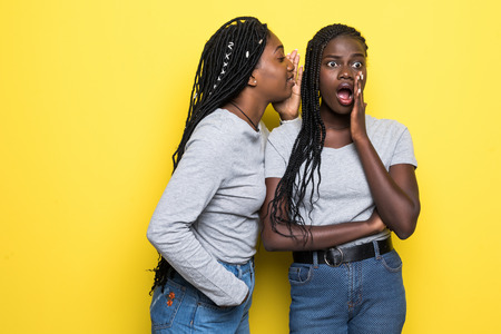 Portrait of two young african women sharing secrets isolated over yellow background