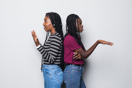 Portriat of two negative african women standing with arms crossed after quarrel over white background