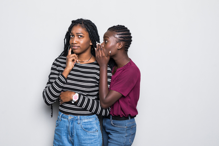 Portrait of two happy young african women sharing secrets isolated