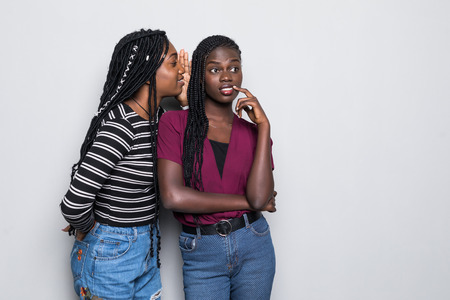 Portrait of two happy young african women sharing secrets over white background 版權商用圖片