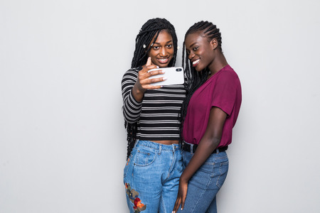 Portrait of two african young girls taking selfie on smartphone isolated over white background