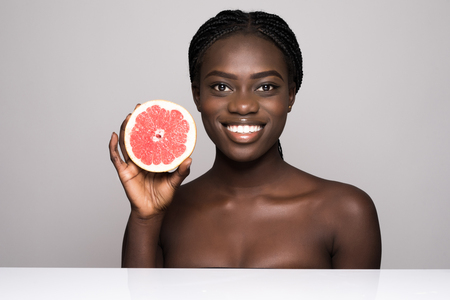 Beauty african woman with orange citrus grapefruit with healthy skin body. Attractive fresh vitamin. Studio shot.