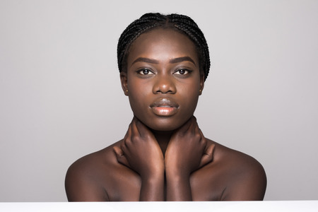 Beautiful afro woman pampering the neck - on white background