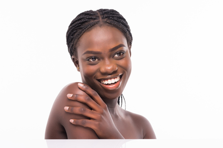 Close up beauty portrait of african beautiful half naked woman applying face cream and looking away isolated over white background Фото со стока