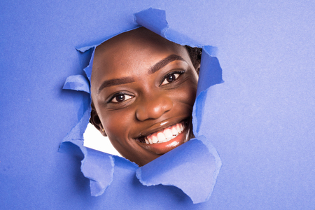The face of a young african girl with a bright make-up and puffy purple lips peers into a hole in violet paper. Stock fotó