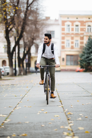 Indian Businessman riding bicycle to work on urban street Imagens