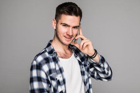 Young casual man looks to side while talking on the phone on white background