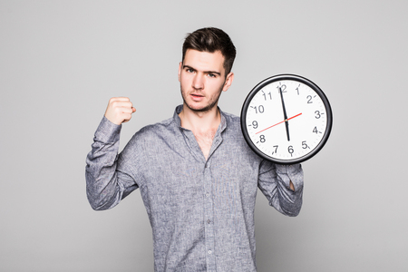 Portrait of a smiling casual man with win gesture on wall clock over gray background 版權商用圖片