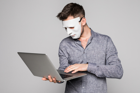 Hacker with anonymous mask with laptop while standing against white background